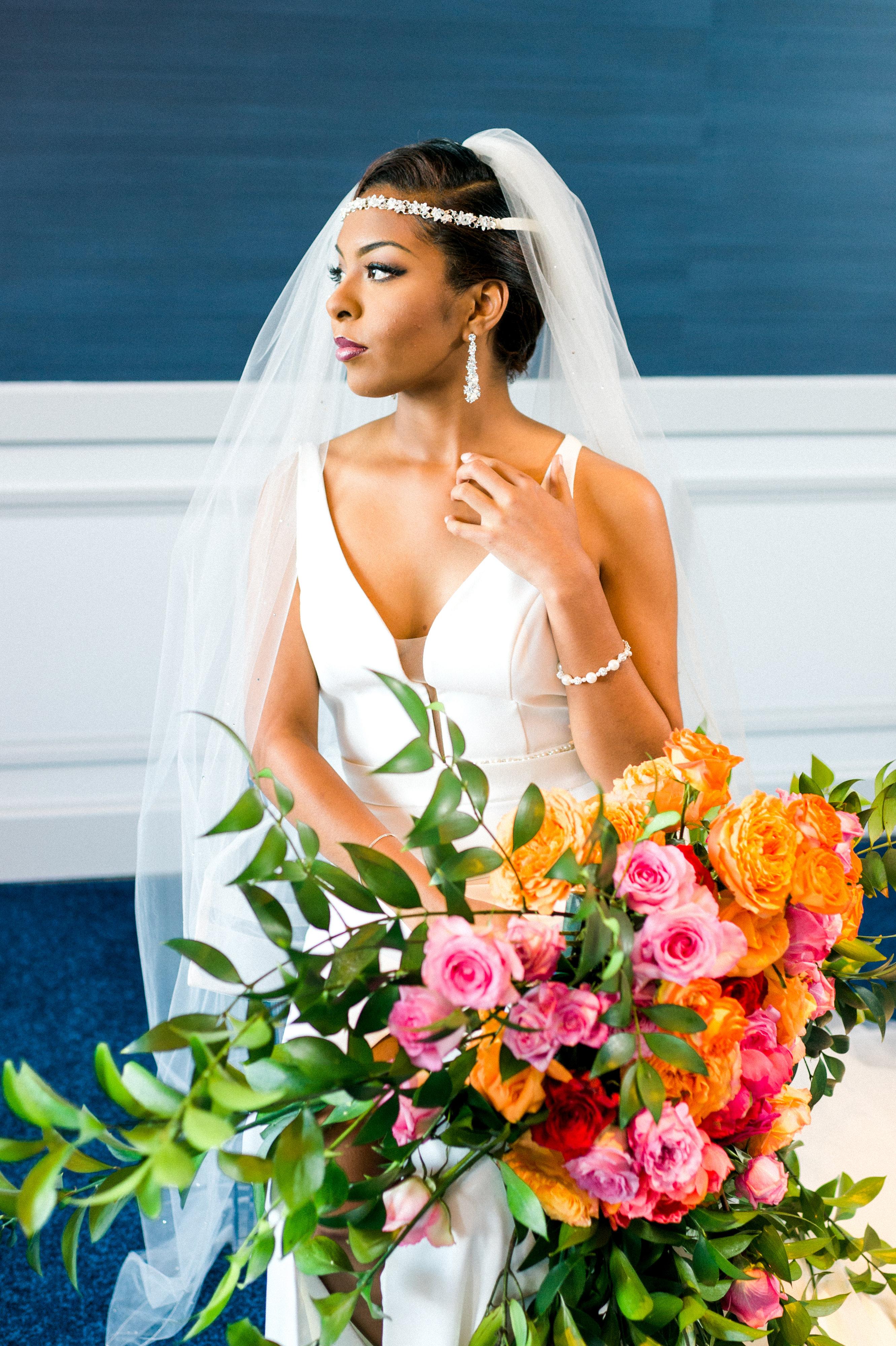 E'MAGNE Events & Co - North Carolina luxury wedding planner - branded logo - orange and navy blue wedding - bride with orange and fuchsia bouquet