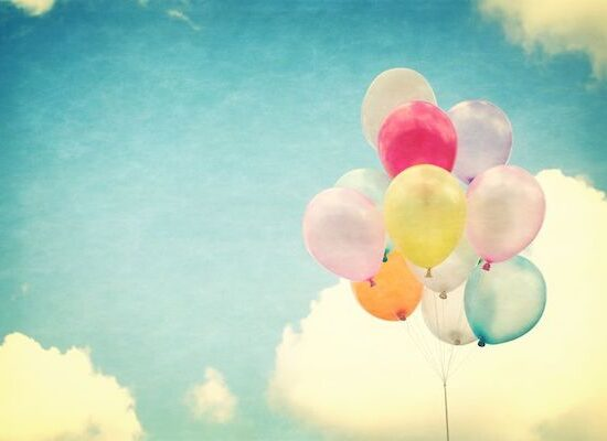 a bunch of colorful balloons floating in the clouds