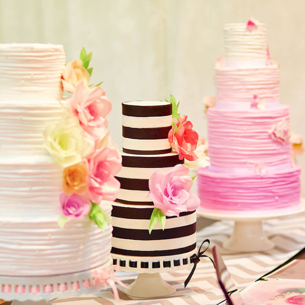 Three different wedding and event cakes on a dessert table