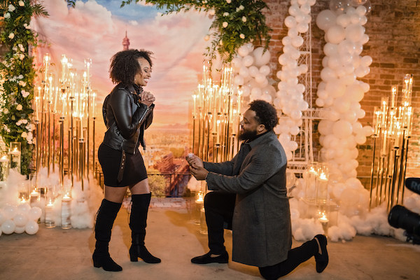 Durham man down on one knee proposing in front of a Paris themed backdrop