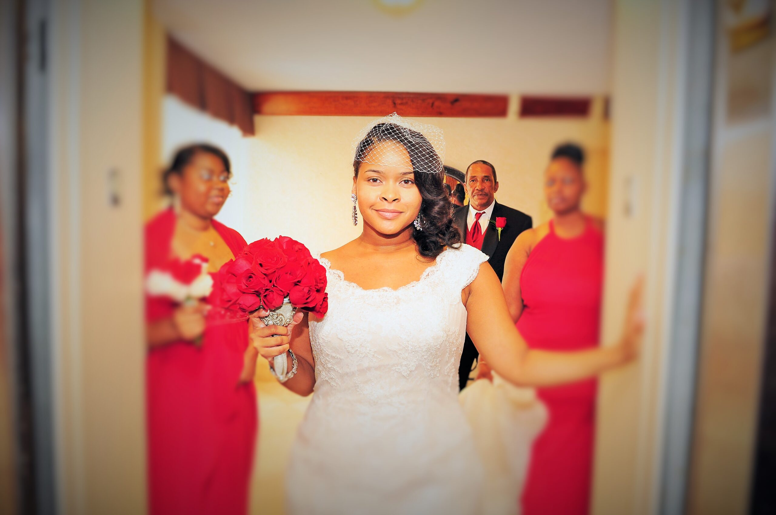 bride posing for photos with her father and rwedding party in the background
